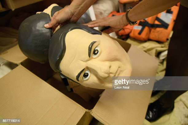 Melanie Kramers of Oxfam holds a mask of former Chancellor of the Exchequer George Osborne while surrounded by assorted props used in political...