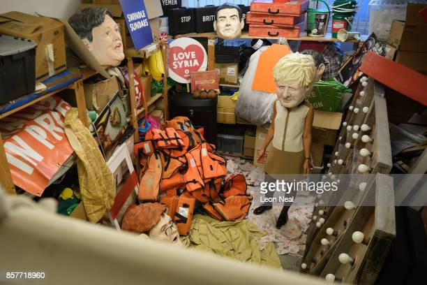 Melanie Kramers of Oxfam poses while wearing a mask of Foreign Secretary Boris Johnson with assorted props used in political campaigns in the store...