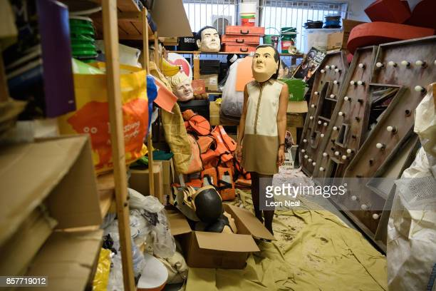 Melanie Kramers of Oxfam wears a mask of former Chancellor George Osborne while surrounded by assorted props used in political campaigns in the store...