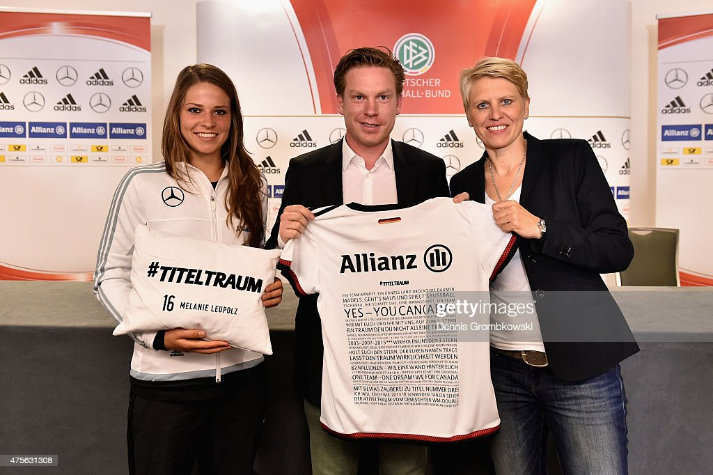Melanie Leupolz and team manager Doris Fitschen of Germany pose with Peter Kort, head of sponsorship Allianz AG, presenting a shirt and a pillow displaying messages of fans during a press conference at The Shaw Centre on June 2, 2015 in Ottawa, Canada.