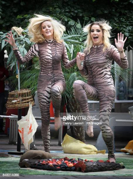 Melanie McDonald and Jodie Waite run on fake hot coals as a section of Buchanan Street Glasgow is turned into a desert island during the launch of a...