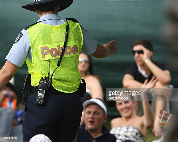 A member of the Australian police advises the crowd at Melbourne Park on day two of the Australian Open tennis tournament in Melbourne 16 January...