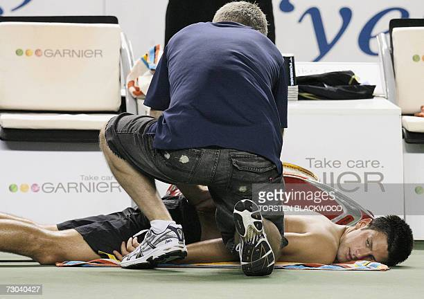 A trainer works on the back of Novak Djokovic of Serbia during an injury time out while playing against Danai Udomchoke of Thailand in the men's...