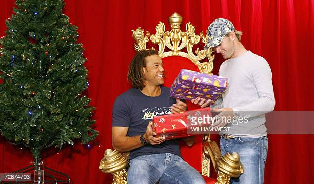Australian cricketers Andrew Symonds and Michael Clarke exchange presents at the team's Christmas party where the players and their families get...