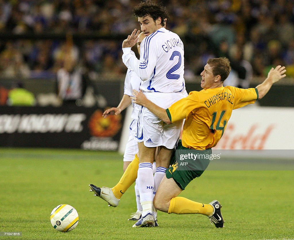Australian defender Scott Chipperfield contests the ball with Greek player Georgios Seitaridis during their football match being played in Melbourne...