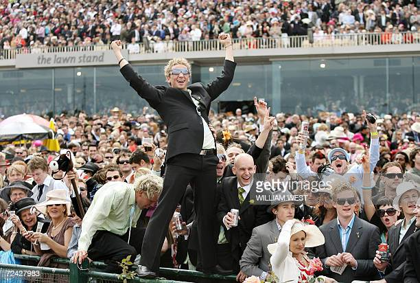 Fans celebrate in the huge crowd as Japanese horse Delta Blues wins the five million Australan dollar Melbourne Cup horse race 07 November 2006 Delta...