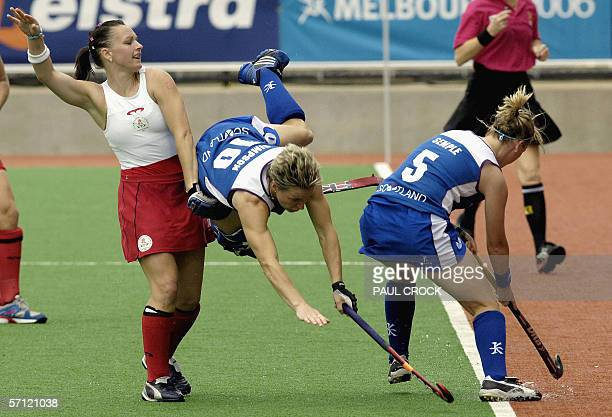 Forward Rhonda Simpson of Scotland dives between England midfielder Jennie Bimson and teammate Catriona Semple during their women's field hockey...