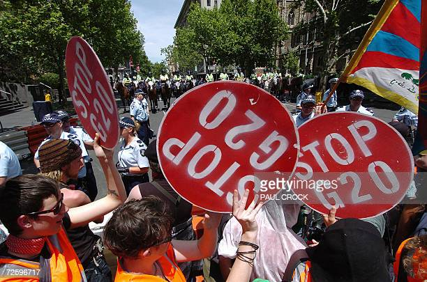 Protestors dance along a police blockade during the G20 finance summit in Melbourne 18 November 2006 Hooded protestors later attacked vehicles and...