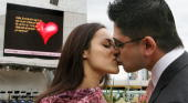 Sayeed David kisses his girlfriend Shella Thomas after proposing via a giant video screen at the launch of a new interactive media service where...