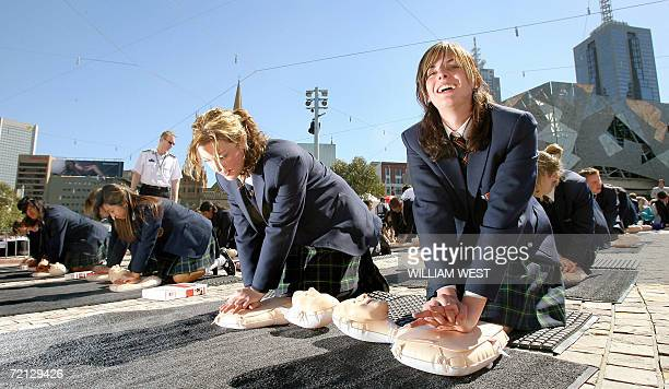 School girls practice giving life saving CPR skill to dummys during a mass teaching by St John Ambulance first aid trainers in Melbourne's Federation...