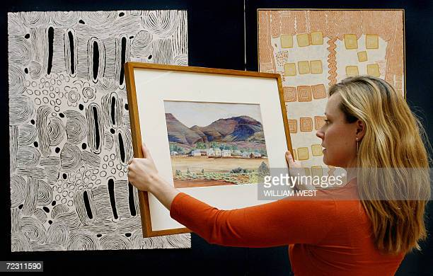 Sotheby's employee Kate Dezarnaulds holds the first painting by famous Aboriginal artist Albert Namatjira painted in 1936 and which is up for auction...