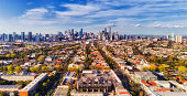Aerial view of Melbourne city CBD high-rise towers from Port Melbourne and Southbank above residential suburb house roofs and local streets, roads, cars and parks.