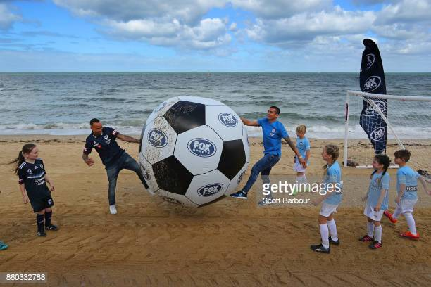 Melbourne City player Tim Cahill and Melbourne Victory's Archie Thompson play a game of beach soccer with kids from Melbourne City and Melbourne...