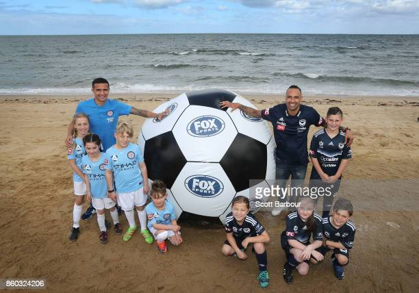 Melbourne City player Tim Cahill and Melbourne Victory's Archie Thompson pose with with kids from Melbourne City and Melbourne Victory junior...