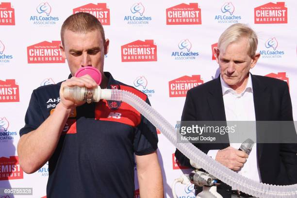 Melbourne Demons head coach Simon Goodwin tests his lung capacity for Men's Health Wellness Week during an AFL media opportunity at the Melbourne...
