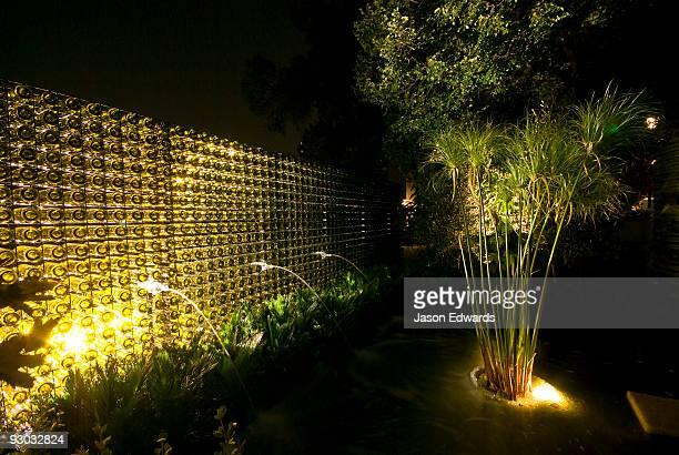 Ornamental lighting illuminates a fountain pond and wine bottle wall.