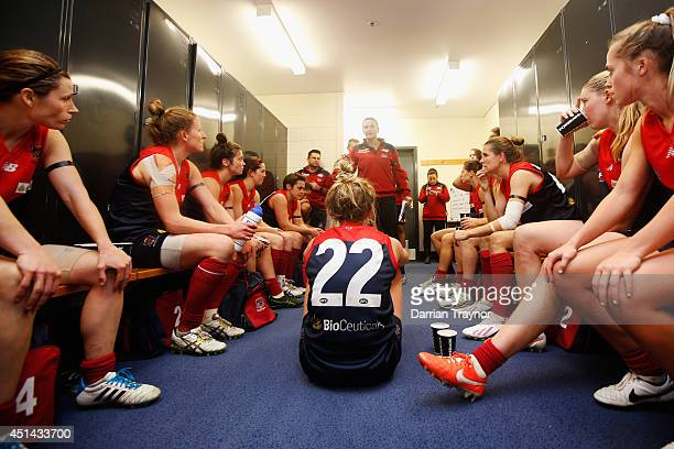 Melbourne players listen to instruction at the half time break during the women's exhibition AFL match between the Western Bulldogs and the Melbourne...