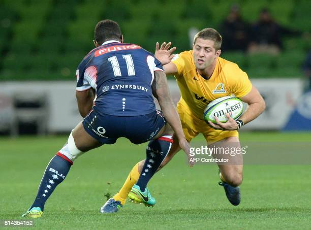 Melbourne Rebels left wing tries to evade a tackle from Argentina's Jaguares right wing Santiago Cordero during the Super Rugby match between...