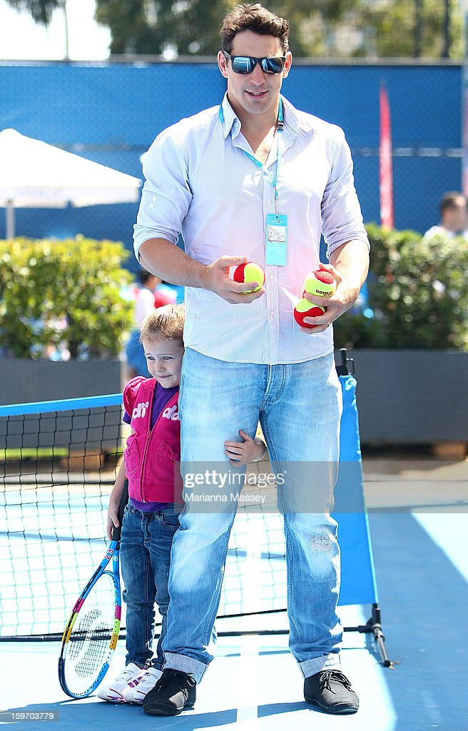 Melbourne Storm NRL player Billy Slater practices hitting the tennis ball with his children Jake and Tyla on the MLC Hotshots mini tennis court during day six of the 2013 Australian Open at Melbourne Park on January 19, 2013 in Melbourne, Australia.
