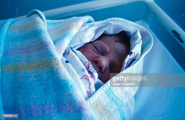 A newborn baby infant wrapped snuggly in a warming blanket.