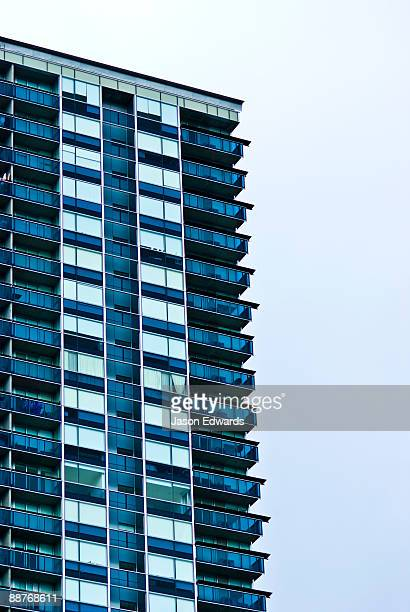 Balconies in a highrise apartment complex look into an empty skyline.