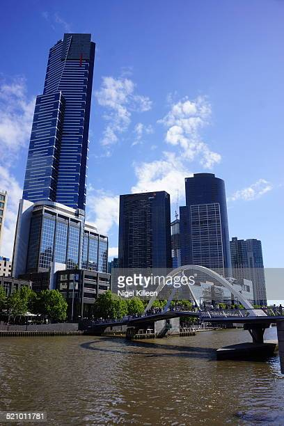 Melbourne's iconic Eureka tower sits on the south bank of the Yarra River with the SouthBank footbridge connecting both sides of the river Melbourne...