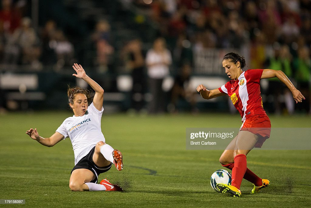 Meleana Shim #6 of Portland Thorns FC slides in defense of Western New York Flash's Carli Lloyd #10 in the National Women's Soccer League Championship at Sahlen's Stadium August 31, 2013 in Rochester, New York.