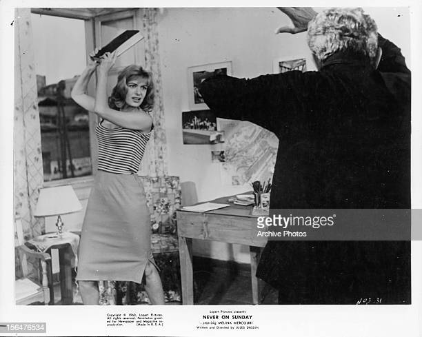 Melina Mercouri threatens a man with a book in a scene from the film 'Never On Sunday' 1960