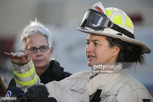 Melinda Drayton right Battalion Chief for the Oakland Fire Department speaks at a press conference regarding the warehouse fire that has claimed the...