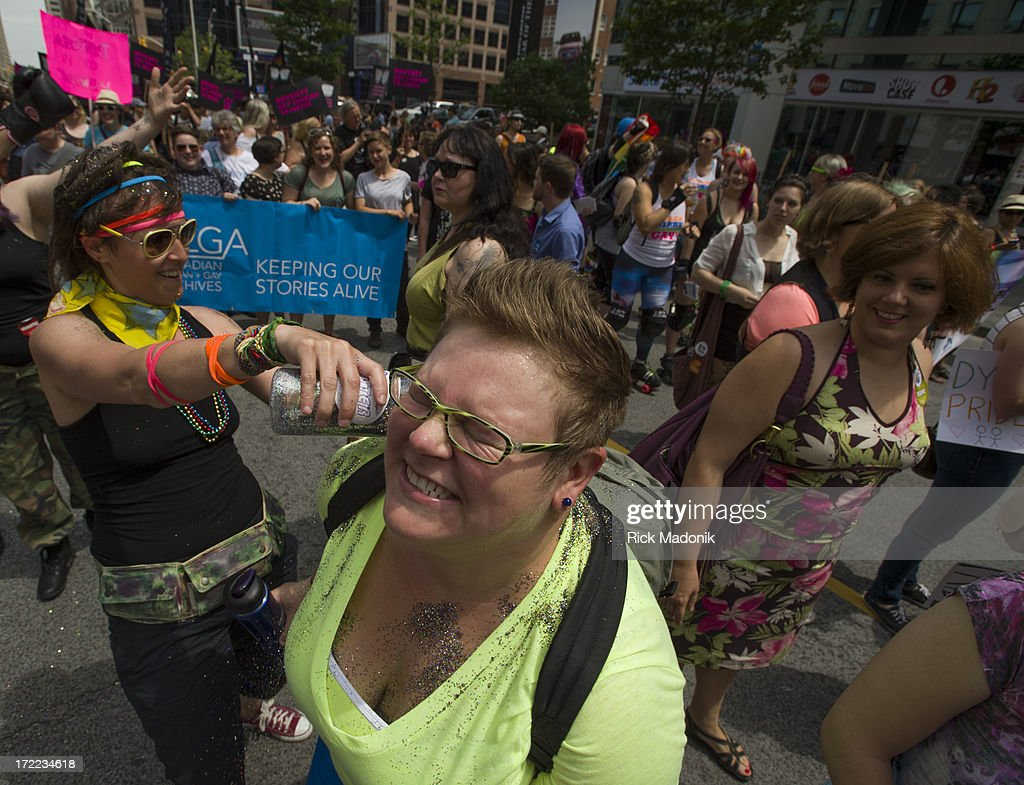 Melissa Carroll (left) sprinkles glitter on marchers. Pride Toronto Dyke March works its way through the downtown core as marchers celebrate Pride Toronto festivities, on Saturday, June 29, 2013. The larger extravaganza of the Pride Parade is set for Sunday.