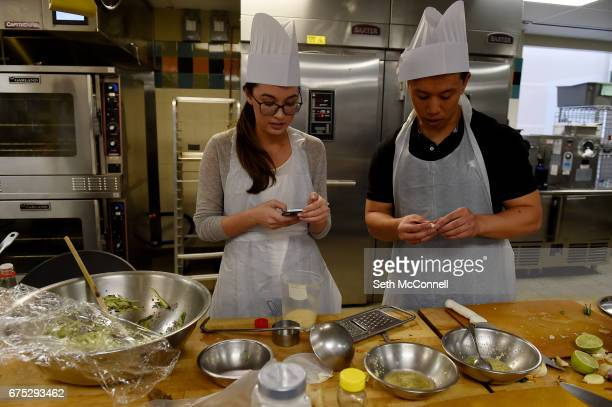 Melissa Laughter left checks a recipe on her phone as she helps Alan Quach make a sauce for their shumai at Vail Hall on the campus of Johnson Wales...