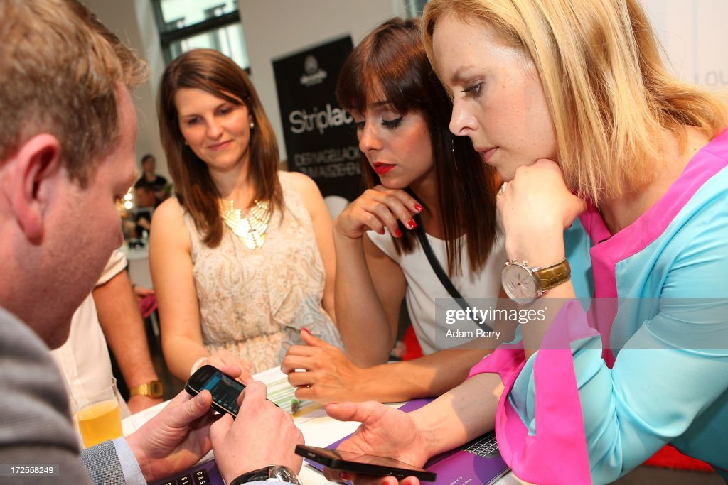 Melissa Otiz Gomez (2 from R) and Isabel Edvardson (R) receive a demonstration of a Blackberry Z10 smartphone at the Blackberry Style Lounge during Mercedes-Benz Fashion Week in Berlin on July 3, 2013 in Berlin, Germany.