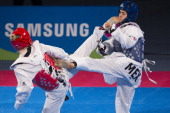 Melissa Oviedo of Mexico competes with Nina Klaey of Switzerland during a women's 62 kg combat of WTF World Taekwondo Championships 2013 at the...
