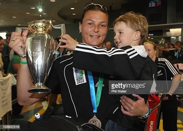 Melissa Ruscoe captain of the New Zealand Black Ferns holds the trophy with her nephew Logan Dear as the team arrives at Auckland Airport after the...
