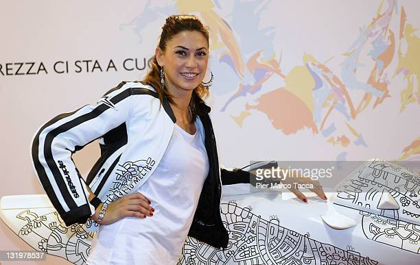 Melissa Satta wears the bike leathers that will be auctioned online on ebay for the family of Marco Simoncelli at the EICMA 2011 69th International...