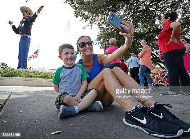 Melissa Steed makes a selfie with Lincoln Jones with the State Fair of Texas one week away as crews put up the iconic Big Tex at the north end of the...