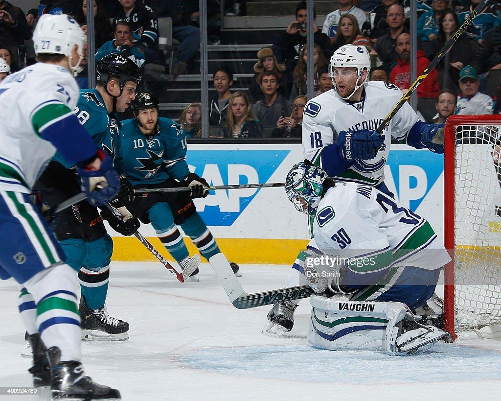 Melker Karlsson and Andrew Desjardins of the San Jose Sharks skate in for a rebound attempt against Shawn Matthias Ryan Miller and Ryan Stanton of...