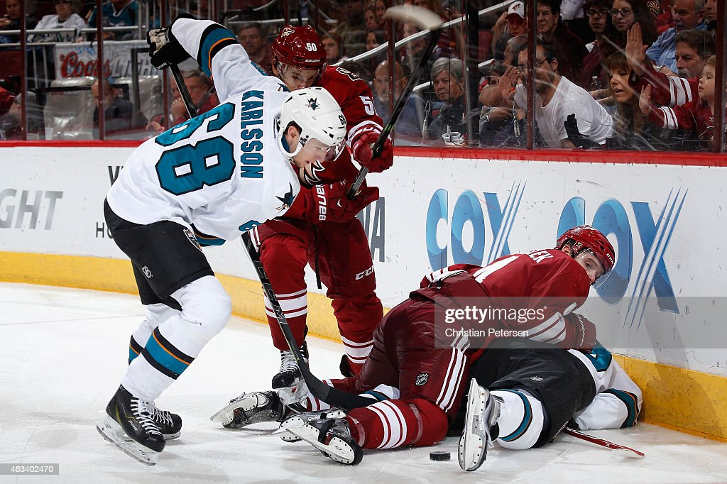 Melker Karlsson #68 of the San Jose Sharks attempts to control the puck under pressure from Antoine Vermette #50 and Zbynek Michalek #4 of the Arizona Coyotes during the third period of the NHL game at Gila River Arena on February 13, 2015 in Glendale, Arizona. The Sharks defeated the Coyotes 4-2.