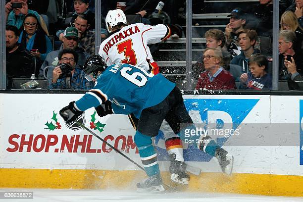 Melker Karlsson of the San Jose Sharks hits Jyrki Jokipakka of the Calgary Flames during a NHL game at SAP Center at San Jose on December 20 2016 in...