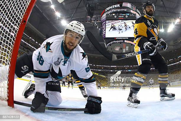 Melker Karlsson of the San Jose Sharks slides into the net after a play against the Pittsburgh Penguins during the first period in Game Two of the...