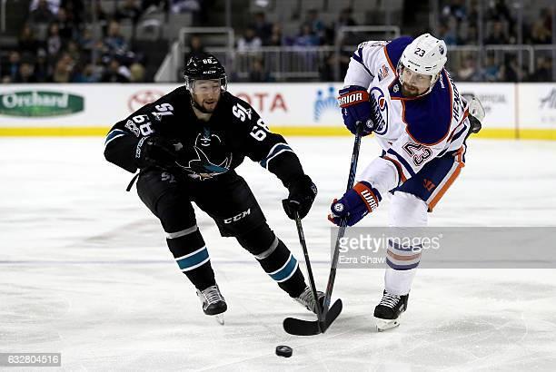 Melker Karlsson of the San Jose Sharks tries to get puck away from Matt Hendricks of the Edmonton Oilers at SAP Center on January 26 2017 in San Jose...