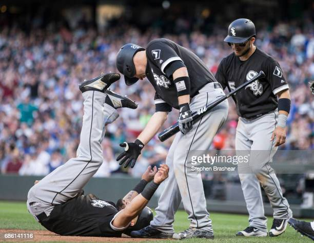 Melky Cabrera left celebrates as Todd Frazier of the Chicago White Sox help him up after scoring a run on a tworun RBI double by Avisail Garcia of...