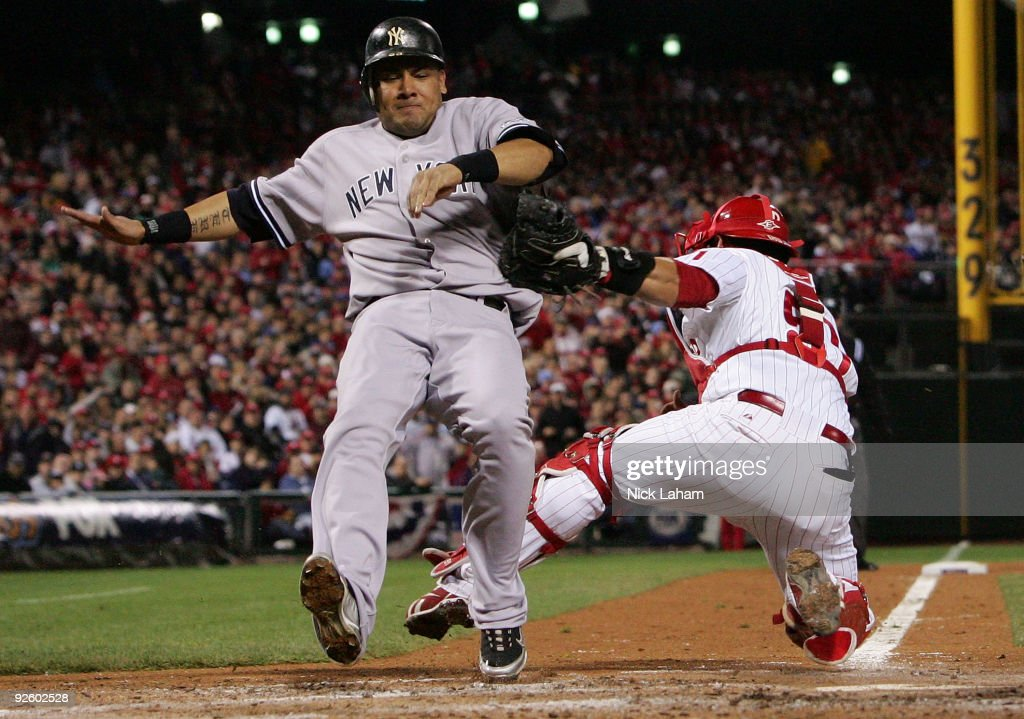 Melky Cabrera of the New York Yankees scores on a RBI single by Johnny Damon in the top of the fifth inning against catcher Carlos Ruiz of the...