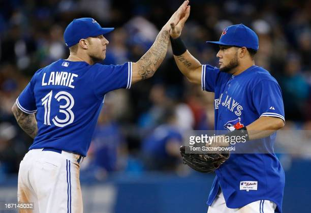 Melky Cabrera of the Toronto Blue Jays celebrates their victory with Brett Lawrie during MLB game action against the New York Yankees on April 21...