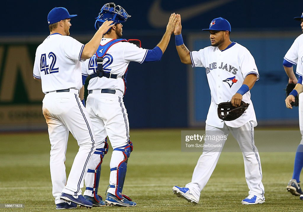<a gi-track='captionPersonalityLinkClicked' href=/galleries/search?phrase=Melky+Cabrera&family=editorial&specificpeople=453444 ng-click='$event.stopPropagation()'>Melky Cabrera</a> of the Toronto Blue Jays celebrates their win with <a gi-track='captionPersonalityLinkClicked' href=/galleries/search?phrase=J.P.+Arencibia&family=editorial&specificpeople=4959430 ng-click='$event.stopPropagation()'>J.P. Arencibia</a> and <a gi-track='captionPersonalityLinkClicked' href=/galleries/search?phrase=Adam+Lind&family=editorial&specificpeople=3911783 ng-click='$event.stopPropagation()'>Adam Lind</a> during MLB game action against the Chicago White Sox on April 15, 2013 at Rogers Centre in Toronto, Ontario, Canada. All uniformed team members are wearing jersey number 42 in honor of Jackie Robinson Day.