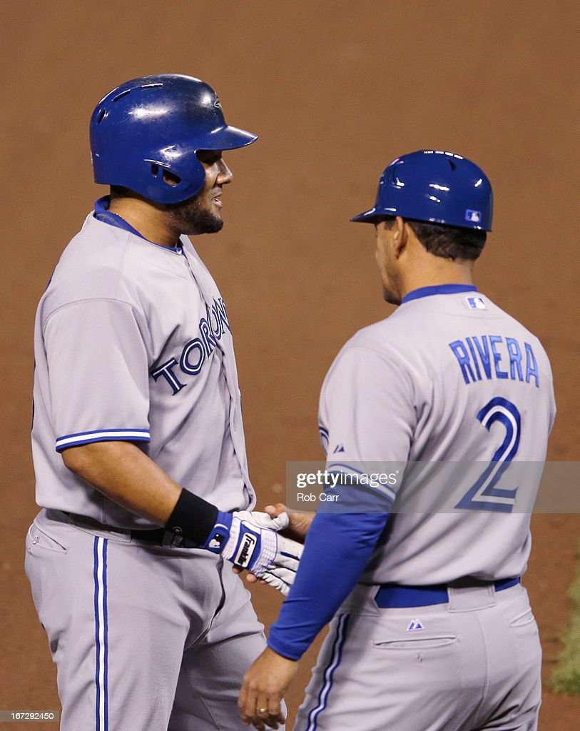 Melky Cabrera #53 of the Toronto Blue Jays is congratulated by third base coach Luis Rivera #2 after hitting a triple against the Baltimore Orioles in the sixth inning of the Blue Jays 4-3 loss at Oriole Park at Camden Yards on April 23, 2013 in Baltimore, Maryland.