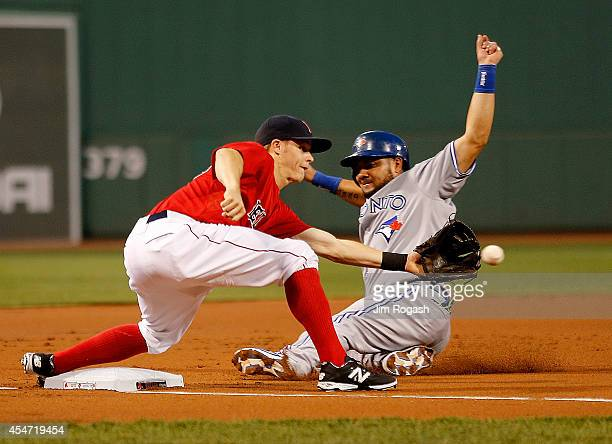 Melky Cabrera of the Toronto Blue Jays moves to third base as Brock Holt of the Boston Red Sox takes a late throw in the first inning against Boston...