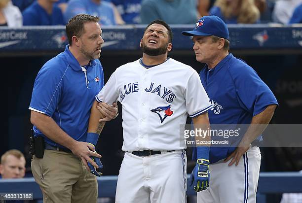 Melky Cabrera of the Toronto Blue Jays reacts after being hit by a pitch in the first inning during MLB game action against the Baltimore Orioles on...