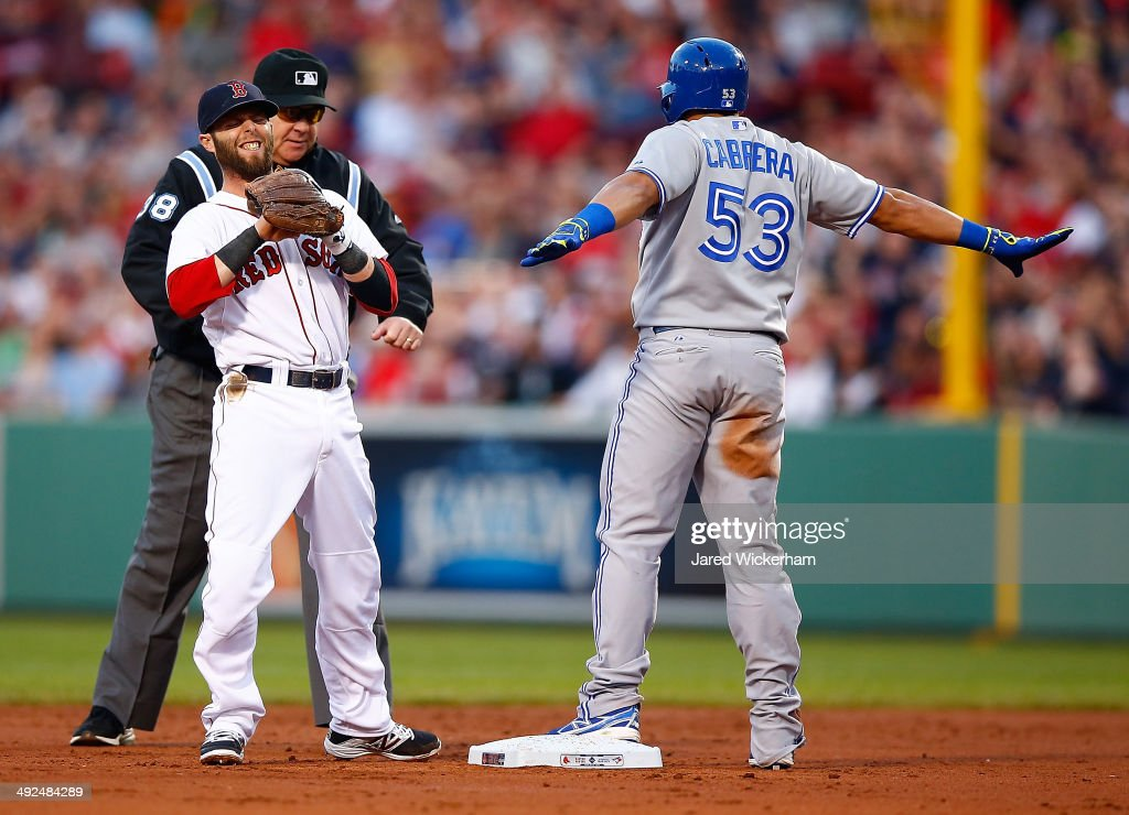Melky Cabrera #53 of the Toronto Blue Jays reacts after sliding safely into second base for a double in the third inning in front of Dustin Pedroia #15 of the Boston Red Sox during the game at Fenway Park on May 20, 2014 in Boston, Massachusetts.