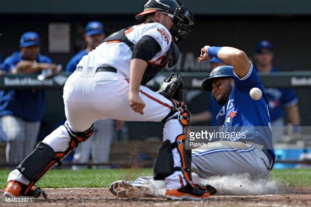 Melky Cabrera of the Toronto Blue Jays slides safe into home plate in front of catcher Matt Wieters of the Baltimore Orioles as he scores off of a...